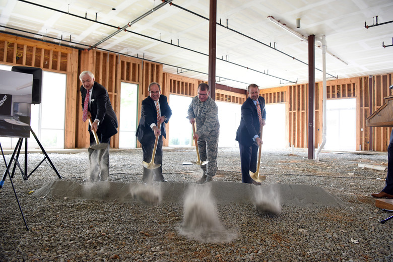 four officials break ground on a new manufacturing plant using shovels