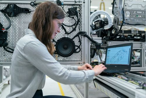 woman engineer in industrial setting searches on laptop